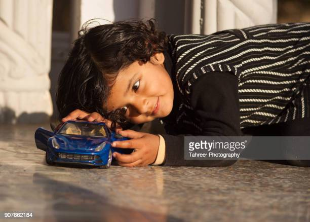 a girl playing with toy car - cute pakistani boys stock photos and pictures