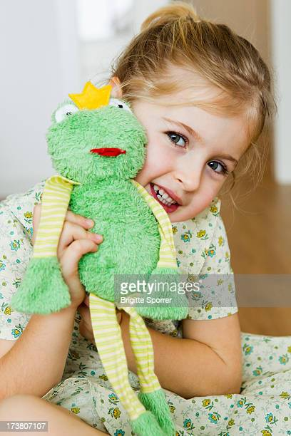 Girl playing with toy frog
