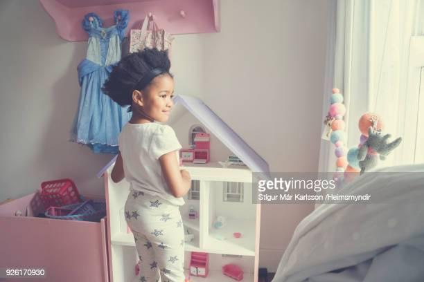 ホームで立ちながらおもちゃで遊ぶ女の子 - ドールハウス ストックフォトと画像