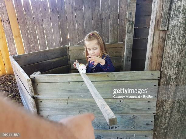 Girl Playing With Toys And Wooden Plank At Yard