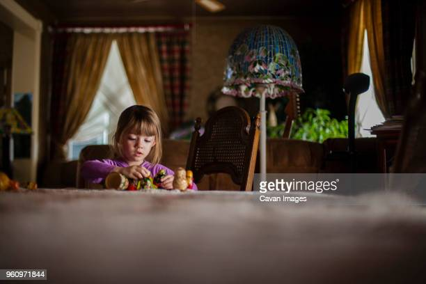 Girl playing with toys at dining table