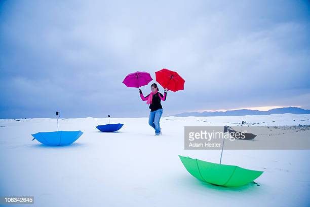 Girl playing with umbrellas on a sand-dune.