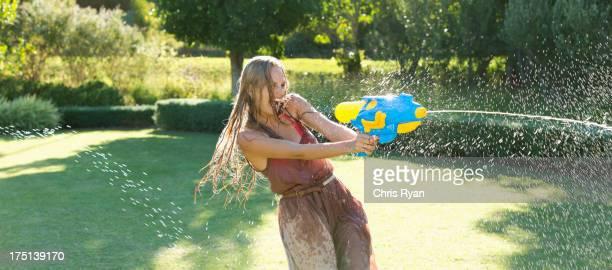 Mädchen spielen mit Wasser Waffe im Garten