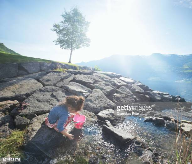Girl playing with water in brook, mountains in background