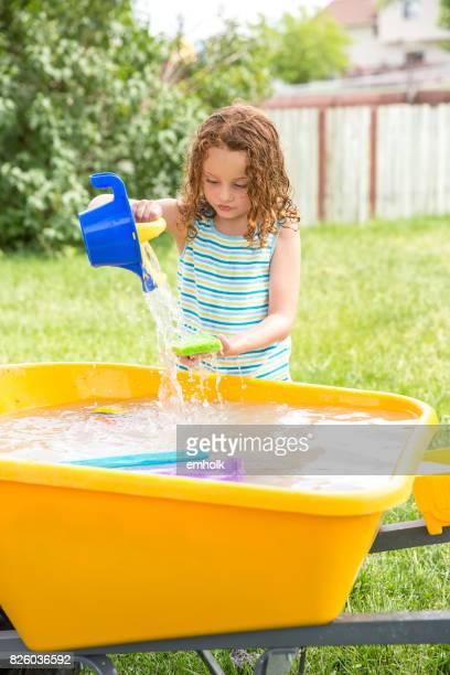 Girl Playing With Water in Wheelbarrow