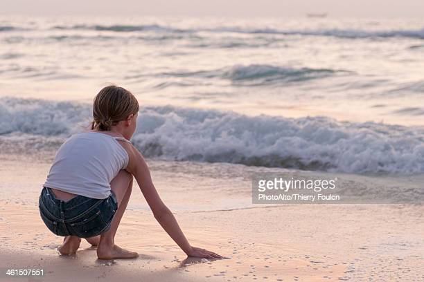Girl playing with water on beach, rear view