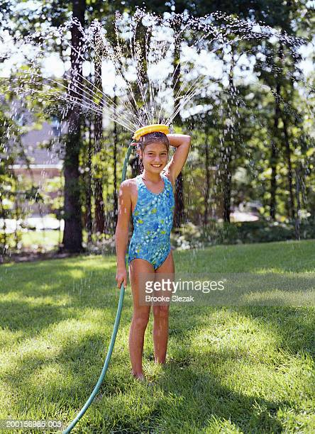 Girl (8-10) playing with water sprinkler