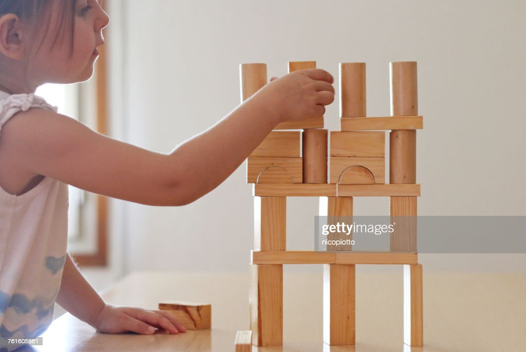 Girl playing with Wooden building blocks : ストックフォト