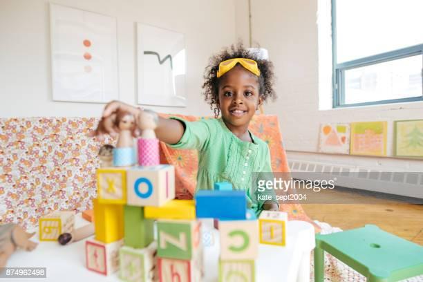 Chica jugando con muñecos de madera