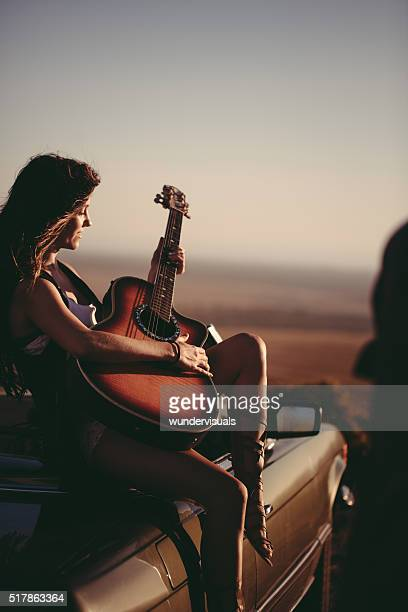 Girl plays acoustic guitar sitting on convertible car at sunset