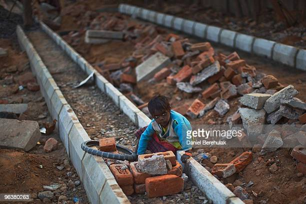 A girl plays at a construction project in front of the Jawaharlal Nehru Stadium on February 03 2010 in New Delhi India The children accompany their...