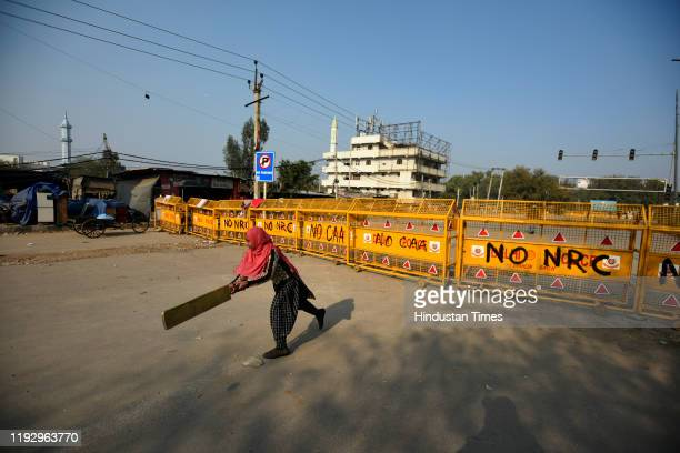 A girl plays cricket on a blocked road during a sitin protest against Citizenship Amendment Act National Population Register National Register of...