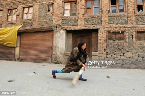 Girl plays cricket on the street during restriction on March 7, 2018 in downtown area of Srinagar, India. Authorities today imposed restrictions in...