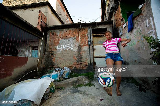 A girl plays football during the 2014 FIFA World Cup Brazil Final between Germany v Argentina in the Mangueira pacified community or shantytown which...