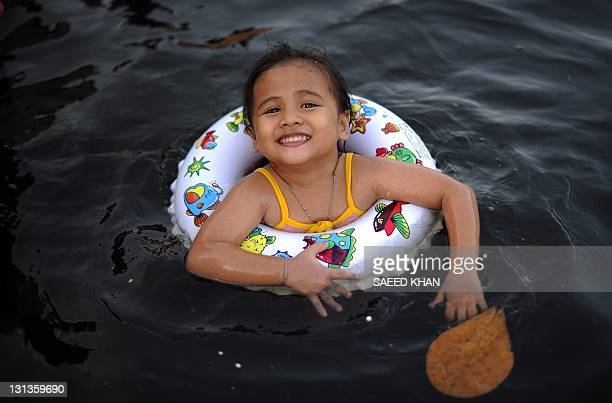 A girl plays in the floodwaters near the overflowing Chao Praya river in Bangkok on November 3 2011 Thai authorities warned flood victims of an...