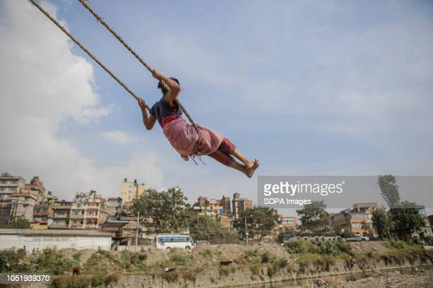 A girl plays on a traditional swing locally known as ëpingí during the Hindu festival Dashain Dashain festival is one of the biggest religious...