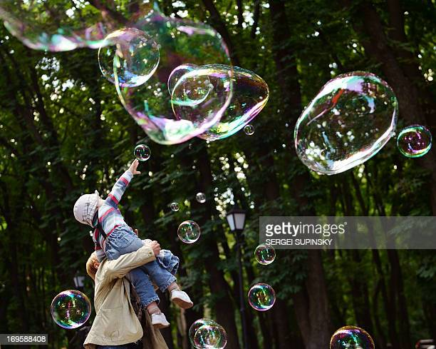 A girl plays on May 28 2013 with soap bubbles during the Share Drive of Life charity event organized by the Kiev Chapter Ukraine motorcycling club...