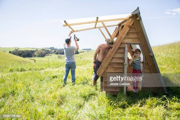 girl plays whilst adults build an a frame cabin in a field - simple living stock pictures, royalty-free photos & images
