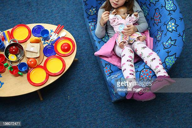 A girl plays with a baby doll at a day care center for children aged 12 months to six years on December 22 2011 in Munich Germany German authorities...