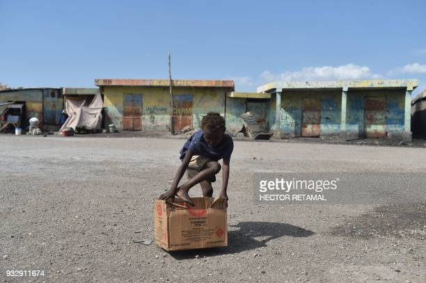 TOPSHOT A girl plays with a cardboard box on a street near the wharf of Cite Soleil in the commune of Cite Soleil PortauPrince on March 14 2018 Book...