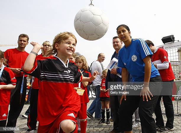 A girl plays with a football next to Steffi Jones head of the Organising Committee of the FIFA Women's World Cup 2011 during the FIFA U20 Women's...