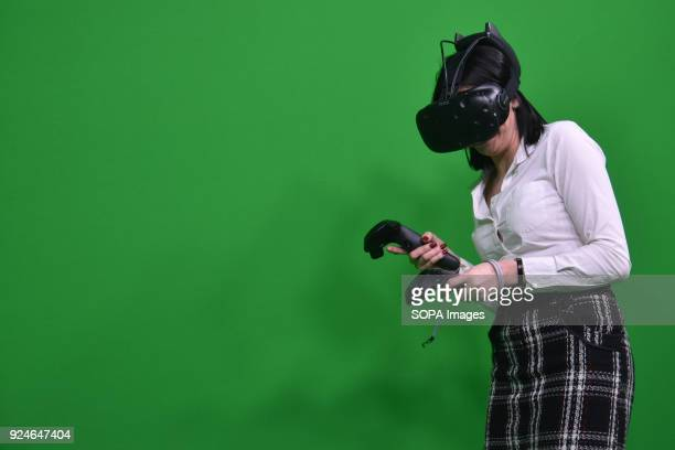 A girl plays with a prografa computer and virtual reality glasses at the mobile world congress The Mobile World Congress 2018 is being hosted in...