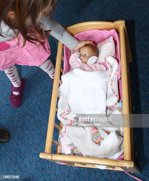 A girl plays with baby doll at a day care center for children aged 12 months to six years on December 22 2011 in Munich Germany German authorities...