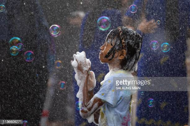 TOPSHOT A girl plays with soap suds during celebrations for the Thingyan festival also known as the Buddhist New Year in Yangon on April 13 2019