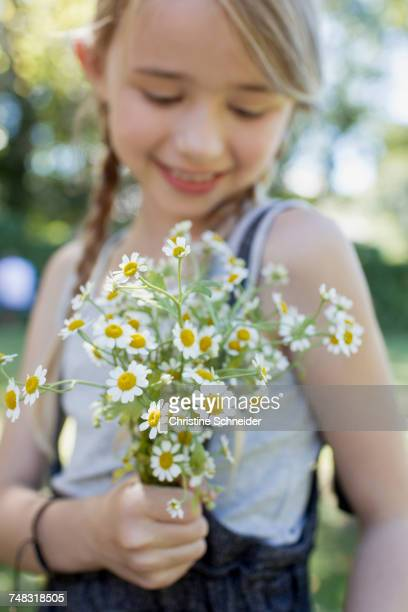 Girl pleased with bunch of camomile flowers