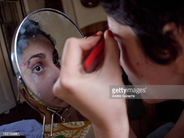 Girl plucking her eyebrows in the mirror