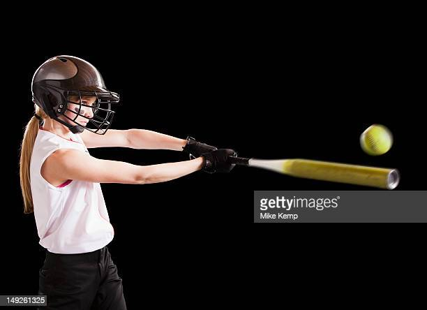 Girl (12-13) plying softball, studio shot