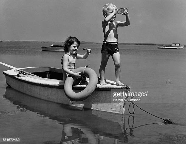 girl pointing and boy looking towards through binoculars while playing on motor boat - {{relatedsearchurl(carousel.phrase)}} stock pictures, royalty-free photos & images