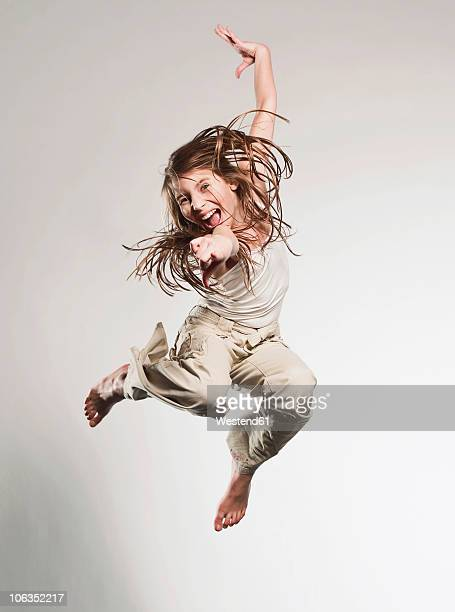 Girl (10-11) pointing and jumping, portrait