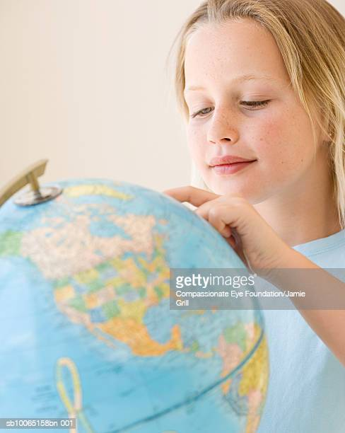 Girl (8-9) pointing at point on globe, close-up