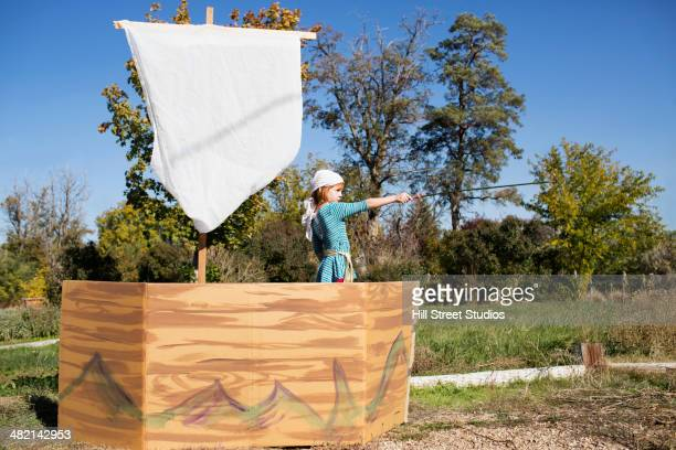 Girl pointing sword from pretend pirate ship
