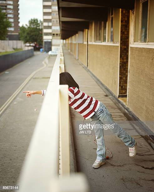 Girl pointing through railings on housing estate