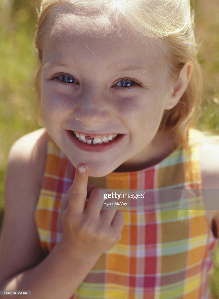 Girl (6-7) pointing to missing tooth, portrait, close-up : Stock Photo
