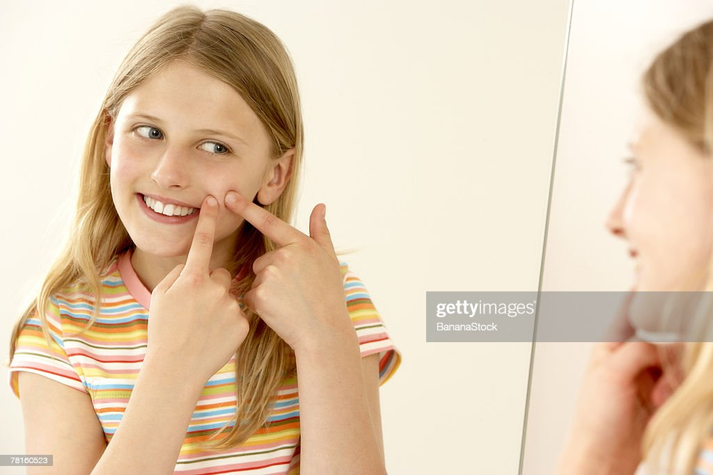 Girl popping pimple : Stock Photo