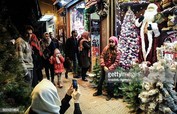 A girl pose for a photograph in front of Christmas store at Mirzayeh Shirazi district where mostly Armenian people live in Tehran Iran on December 24...