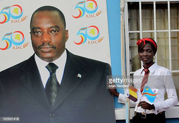 A girl poses beside a portrait of Congolese President Joseph Kabila at INPP where Congolese can learn different skills on June 29 2010 in Kinshasa...