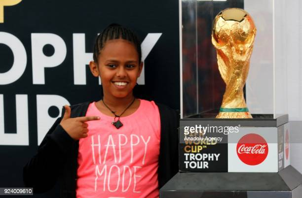A girl poses for a photo near the World Cup Trophy at Hilton Hotel after the trophy was brought to Ethiopia within the 2018 FIFA World Cup Trophy...