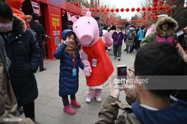 A girl poses for a photo with a Peppa Pig figure at a temple fair in Beijing on the second day of the Lunar New Year on February 6 2019 China is...