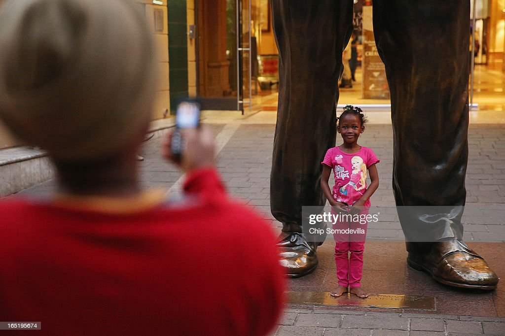 A girl poses for a photograph in front of the 20-foot-tall statue of former South African President Nelson Mandela in the shopping square named after the anti-apartheid hero April 1, 2013 in Johannesburg, South Africa. Mandela, 94, is recovering from pneumonia in hospital, his third stay in the last four months. Mandela's lungs were damaged when he contracted tuberculosis during his 27 years in the infamous Robben Island prison. Mandela became the nation's first democratically elected president in 1994 following the end of apartheid.