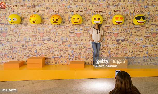 A girl poses for photos with emoji hats fixed on a wall in a shopping mall on May 26 2016 in Guangzhou China Feature China / Barcroft Images...