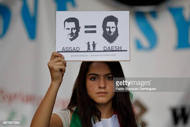 A girl poses for pictures as she holds a placard reading 'Assad equal to DAESH' during a demonstration to show solidarity and support for refugees on...