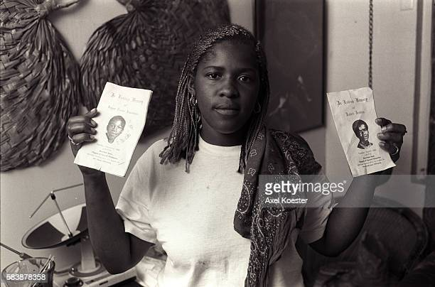 A girl poses holding funeral programs of two recently killed Grape Street members The Grape Street Watts Crips are a mostly African American street...