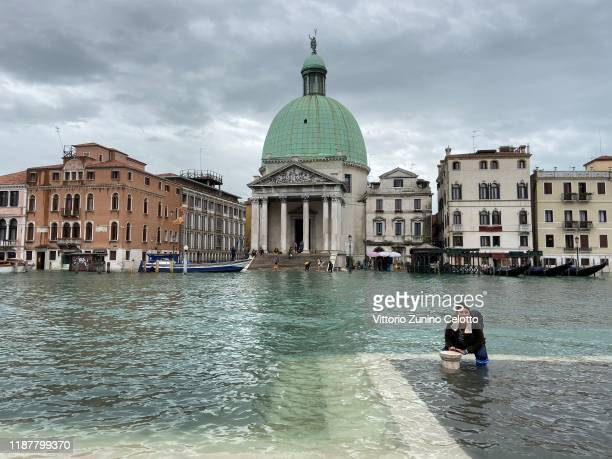 A girl poses smiling days after the second highest tide from 1966 on November 15 2019 in Venice Italy