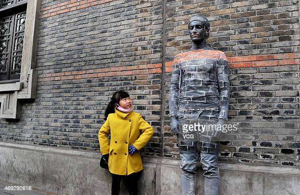 "Girl poses with a boy disguised as a wall near New World street on April 10, 2015 in Shanghai, China. A boy ""hides"" himself by being painted the same..."