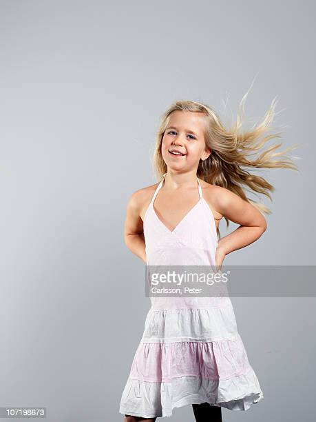Girl posing against grey background, smiling