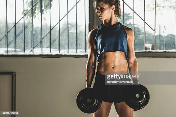 Girl posing in gym with weights